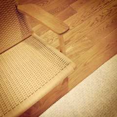 Rattan chair and rug on wooden floor