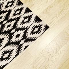 Rug with ethnic design on wooden floor