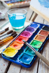 Set of watercolor paints,  art brushes,  glass of water and ease