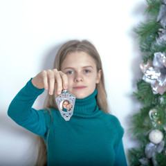 Young girl with a Christmas light. Reiterative   picture.