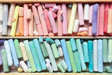 Pastel crayons in wooden artist box closeup, top view.