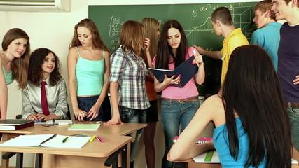 Group student near green blackboard in classroom.