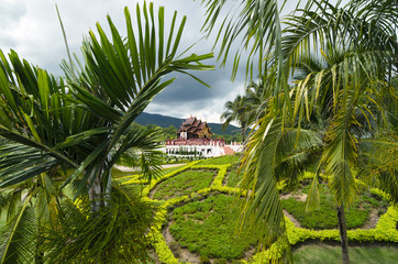 View to the traditional Thai temple in a garden through palm lea