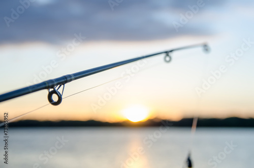 Fotobehang Kust fishing rod with lure at sunset over a lake