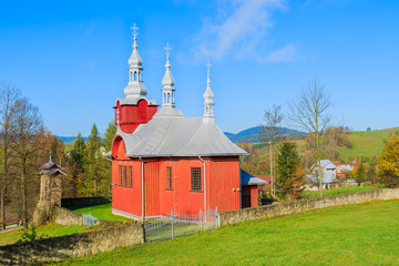 Red wooden church on green meadow in Czyrna village, Poland