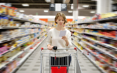 woman with shopping list pushing cart in supermarket