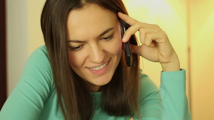 Smiling young woman talking on phone, close up