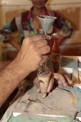Hombre haciendo dibujos con arena.
