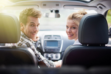 couple sitting in a car looking at camera