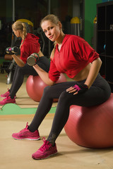smiling fit girl doing exercises with dumbells at gym