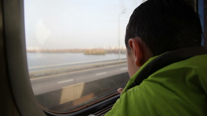 boy looking out the window at the cars in the metro 1