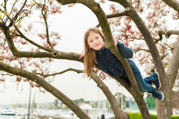 Cute little girl playing on magnolia tree in early spring