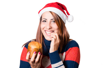 young woman with santa claus hat tasting a Panettone.