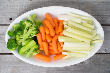 Vegetable tray with celery, broccoli, carrots on a wooden table