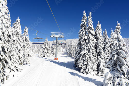 Winter landscape with chairlift and slope at alpine ski resort
