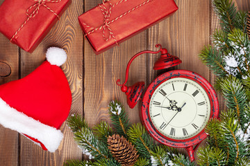 Christmas wooden background with clock, fir tree, gift boxes and