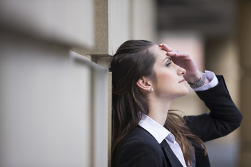 Businesswoman banging her head against a wall.