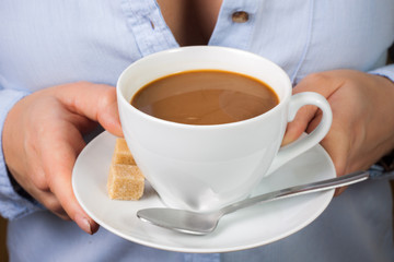 Hand holds mug of coffee with milk with spoon and brown sugar