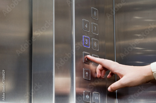 Female finger presses the button for the elevator - 73868129