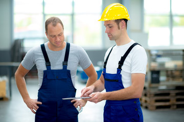 two young worker in factory using tablet pc