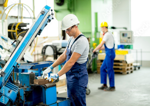 worker with goggles and helmet on the machine - 73869395
