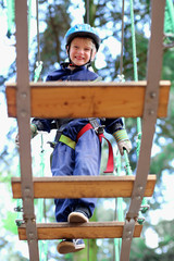 Happy boy climbing in adventure park