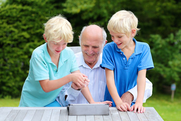 Two brothers teaching grandpa to use tablet pc