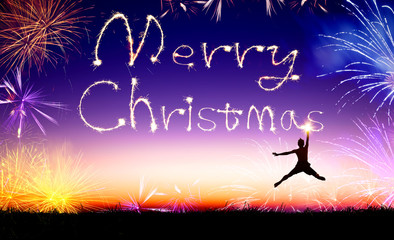 young man jumping and drawing the merry christmas