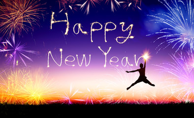 young man jumping and drawing the happy new year