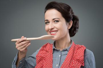 Female cook tasting a recipe