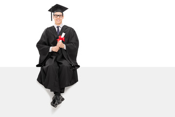 College graduate sitting on a blank billboard