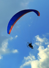 Paragliding man against blue sky