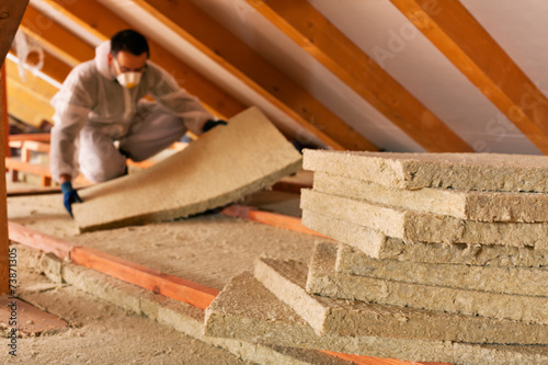 Man laying thermal insulation layer under the roof - 73871305