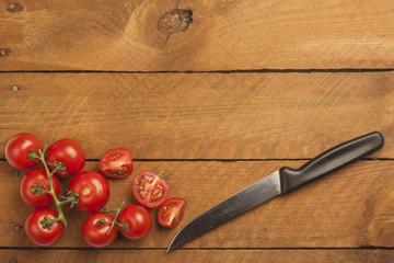 Tomaten, in Teile geschnitten, Messer auf Holz