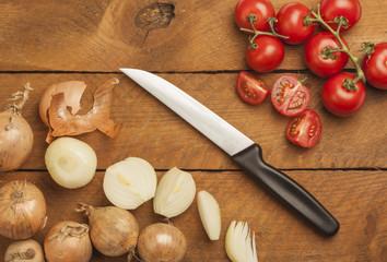 Zwiebeln und Tomaten, geschnitten, Messer, Holz