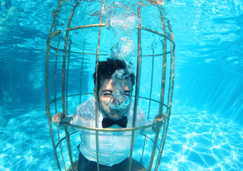 Funny groom underwater in a bird cage