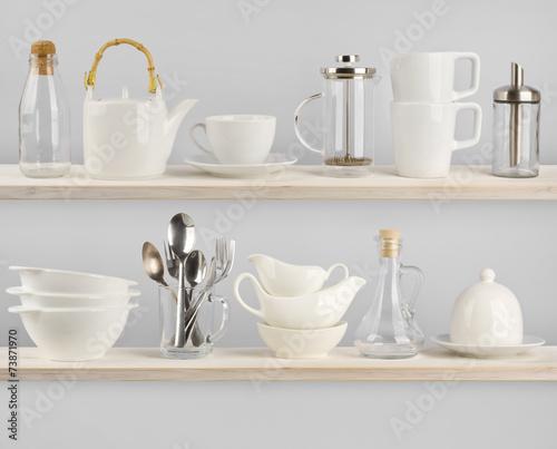 Various kitchen utensils on wooden shelves - 73871970