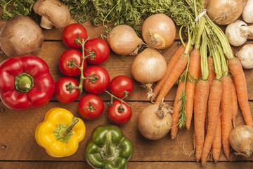 Tomaten, Paprika, Karotten, Zwiebeln und Pilze auf Holz