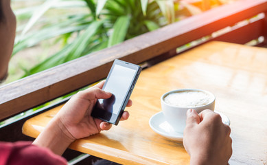 man drink coffee and use smart phone in coffee shop at evening