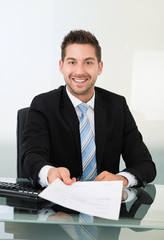 Happy Businessman Giving Document At Desk