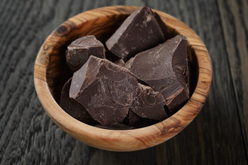 dark chocolate chunks in wooden bowl