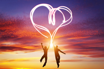 Happy couple in love jump making heart symbol of light