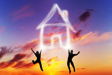 A couple jump and make a house symbol of light. New home
