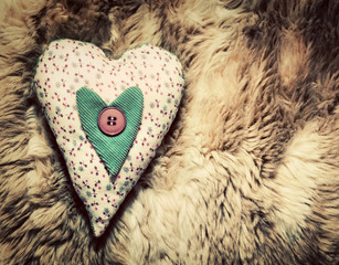 Vintage handmade plush heart pillow on the soft blanket