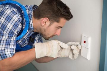 Man Repairing Light Switch At Home