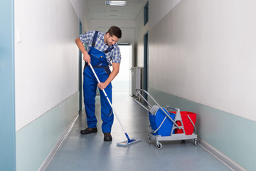 Male Worker With Broom Cleaning Office Corridor