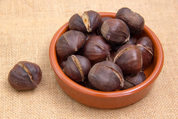 Roasted chestnuts in bowl on placemat jute