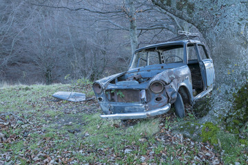 Old car , abandoned in the countryside , rusty .