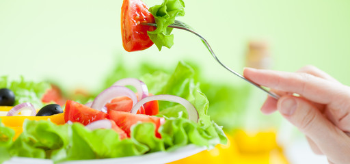 healthy salad eating with vegetables on green background