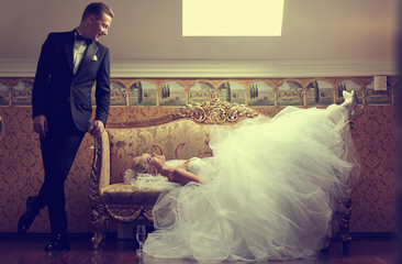 Beautiful bride on a sofa and groom near her in a luxury hotel